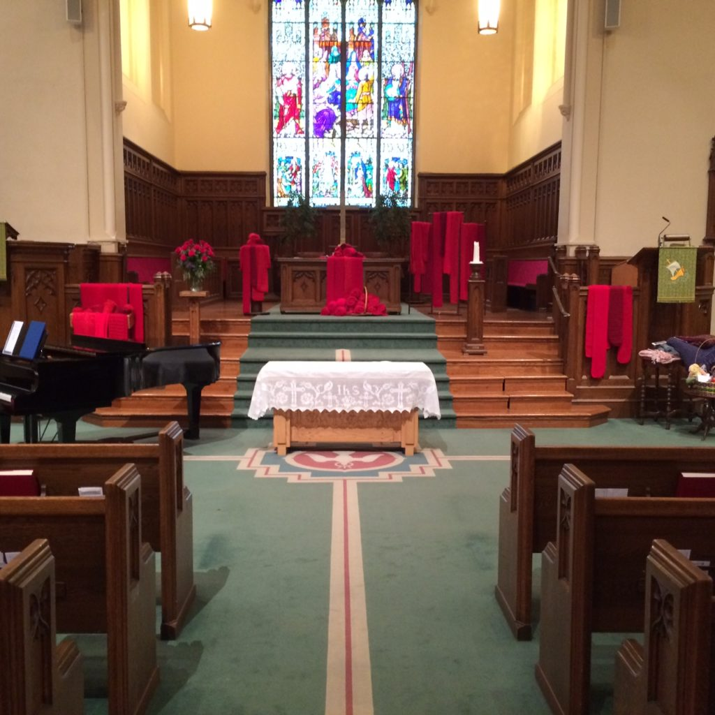 Red scarves knitted at First-St Andrew's  ready for blessing in the sanctuary.