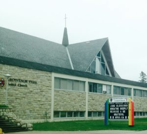 Grosvenor Park United Church's rainbow sign, Saskatoon.  Its two posts are painted bright rainbow.