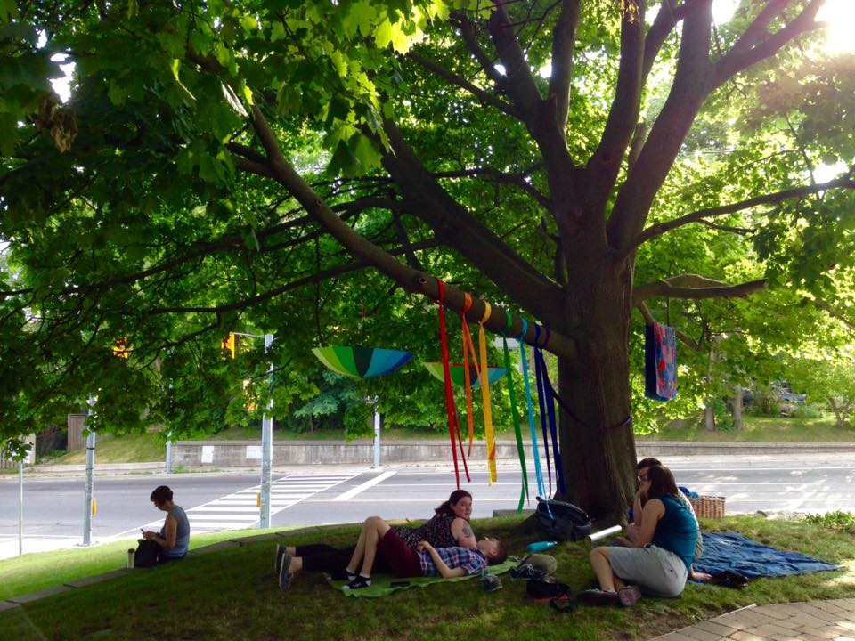 A big maple tree hung with rainbow ribbons and a quilt, with people sitting under it talking.