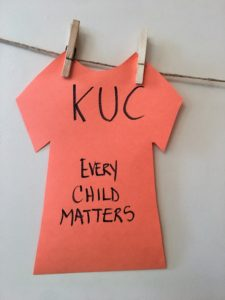 A paper orange shirt pegged to a line. It says KUC Every Child Matters.