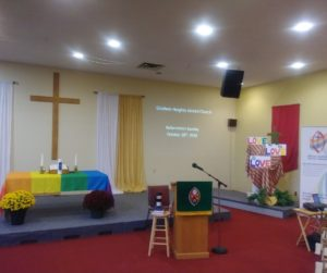 Sanctuary with a wooden cross on the wall, a rainbow cloth on the communion table, a stool, and a pulpit with the United Church crest on it.