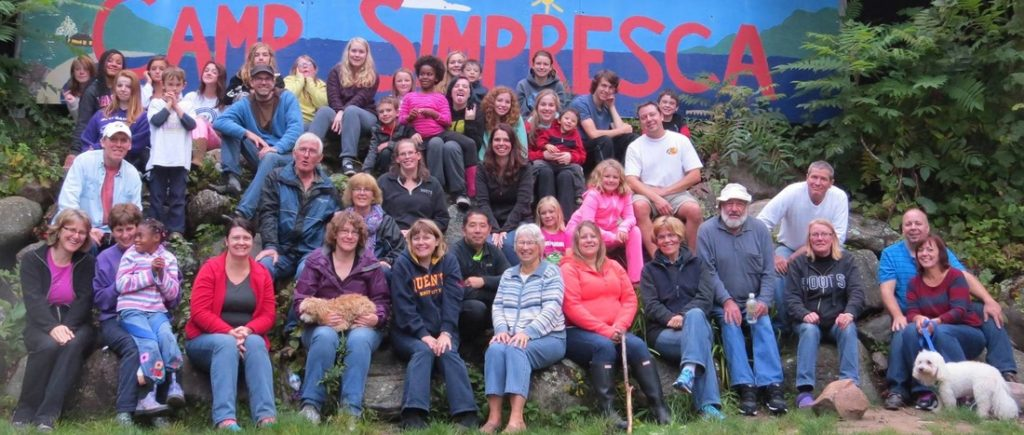 "A group of people of all ages gathered outside in front of a sign saying ""Camp Simpresca""."