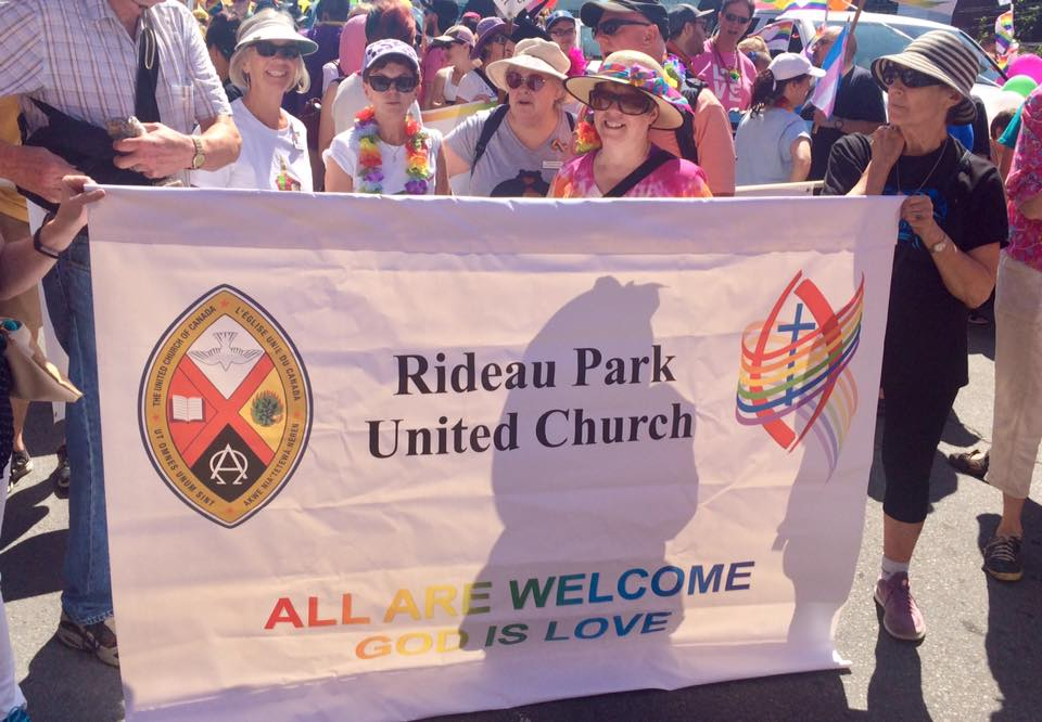 """A group of smiling people stand in the sun behind a white banner with the United Church logo on the left and Affirm's logo on the right. It reads: """"Rideau Park United Church, all are welcome. God is love""""."""